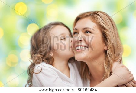 people, happiness, love, family and motherhood concept - happy daughter hugging and kissing her mother over green lights background