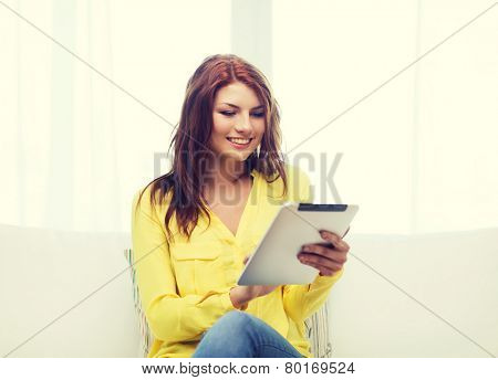 home, technology and internet concept - smiling woman sitting on couch with tablet pc computer at home