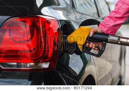Woman filling up car at petrol station black car