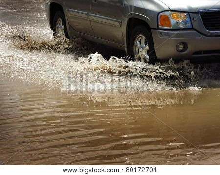 Detail of car driving through flood waters splashing