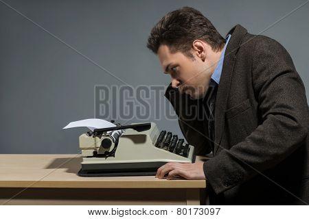 Depressed author sitting at typewriter