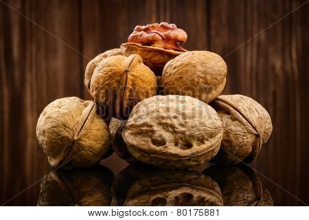 Walnut kernels and whole walnuts on rustic wooden background