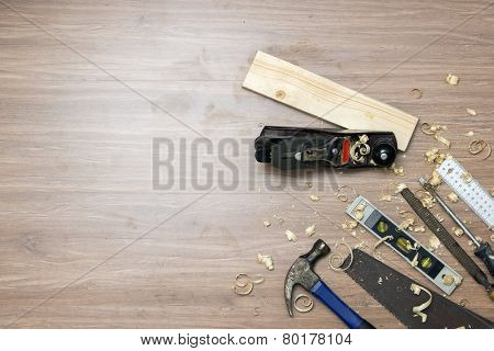 Directly above shot hand jack plane with tools and wood shavings on floor