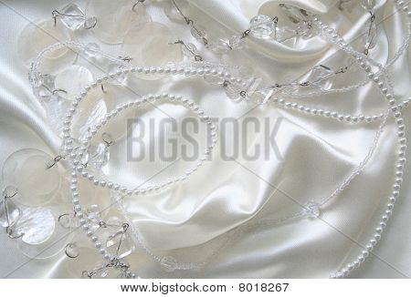 White Pearls And Nacreous Beeds On White Silk As Wedding Background
