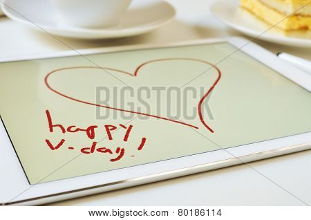 the text happy v-day and a heart drawn in a graphics editor of a tablet on a table set for breakfast