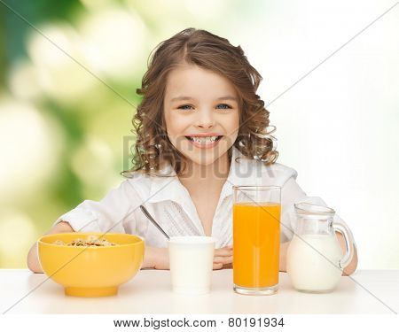 healthy food, eating, people and children concept - happy smiling beautiful girl having breakfast over green background