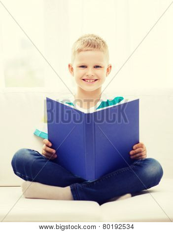 leisure, childhood, education and home concept - smiling little boy reading book and sitting on couch at home