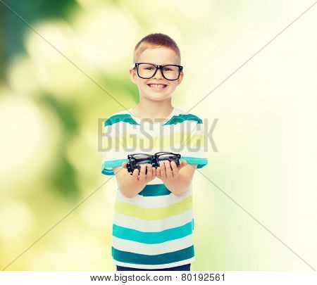 vision, health, ecology and people concept - smiling little boy in eyeglasses holding spectacles over green background