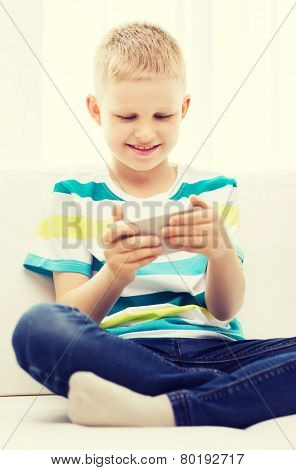 home, leisure, childhood, technology and game concept - little boy with smartphone at home