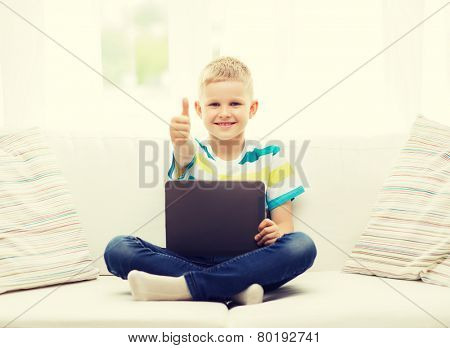 home, leisure and new technology concept - smiling little boy with tablet pc computer at home showing thumbs up