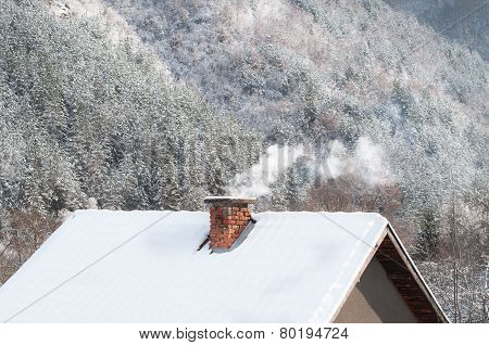 Smoking chimney at winter forest background