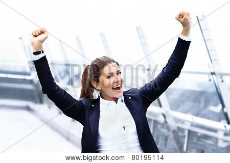 Successful business woman with arms up celebrating