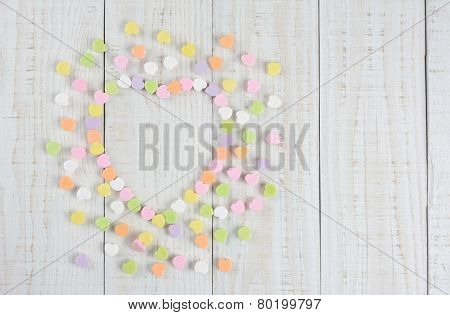 High angle shot of a  group of pastel candy Valentine's hearts forming a larger heart shape on a rustic white wood table. Horizontal format with copy space on a white wood table..