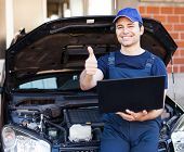 picture of check  - Happy mechanic using a laptop computer to check a car engine - JPG