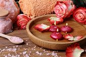 stock photo of unity candle  - Spa concept with roses pink salt and candles that float in a wooden bowl with water - JPG
