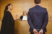 picture of court room  - Lawyer talking with the criminal in handcuffs in the court room - JPG