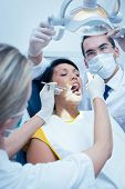 stock photo of dentist  - Male dentist with assistant examining womans teeth in the dentists chair - JPG