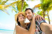 foto of caribbean  - Couple on summer tropical vacation taking selfie photo on the beach - JPG