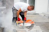 pic of sawing  - Construction worker using a concrete saw cutting stones in a cloud of concrete dust for creating a track - JPG