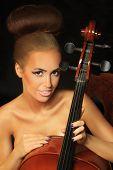 stock photo of cello  - Photo golden beautiful female musician playing a cello - JPG