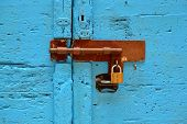 picture of lock  - Locked padlock at closed old blue door - JPG