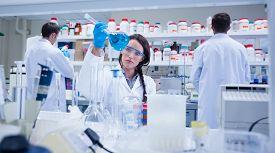 picture of beaker  - Chemist raising beaker of blue liquid with colleagues behind in busy lab - JPG