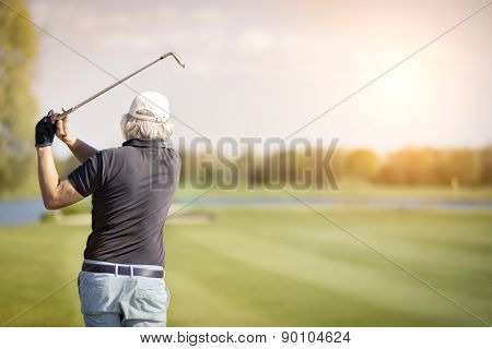 Close up of male senior golf player swinging golf club, with empty copyspace for text.