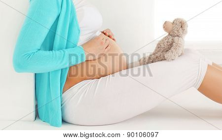 Pregnant Woman Sitting With Teddy Bear Dreams Of A Future Child At Home In White Room Near Window