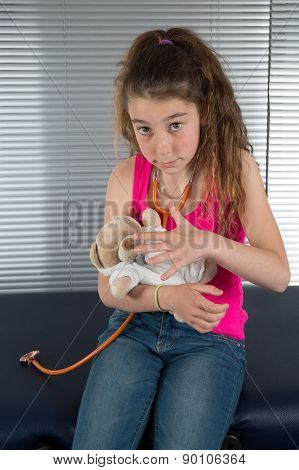 Beautiful Girl Listens By Means Of Stethoscope As Heart Of Toy Bear