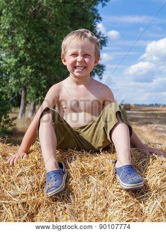 Boy Sitting On Bale Straw