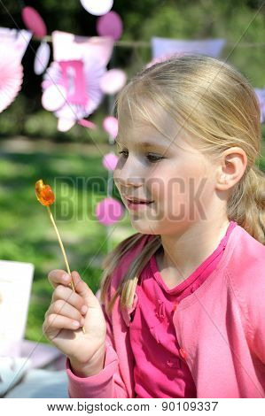 Beautiful little girl looking at a lollipop