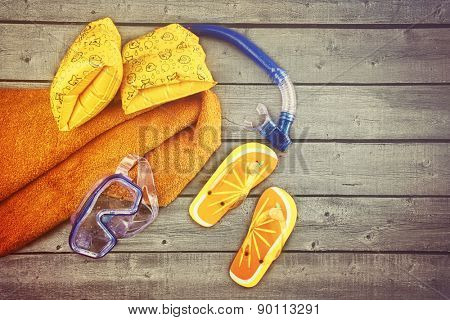 Vacation Concept. Towel and other kids beach toys on wood background
