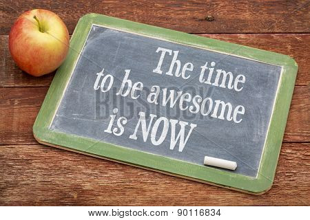 The time be awesome is now - motivational words on a slate blackboard against red barn wood