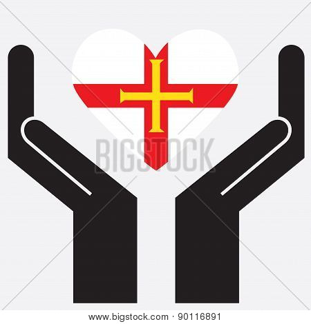 Hand showing Guernsey flag in a heart shape.
