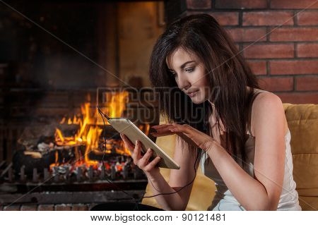 Woman Using Digital Tablet Sitting By Fireplace