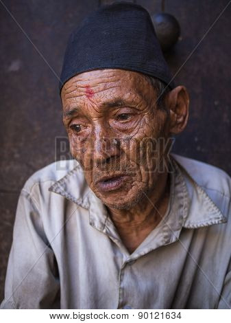 Bhaktapur, Nepal-oct 14 , 2012 : The Old Man Is Sitting In Front Of The Doorway. He Is Waiting For S