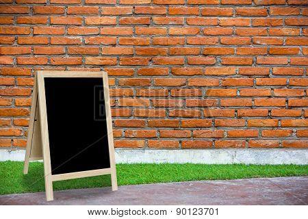 Tripod Blackboard In Interior Room With Molder Brick Wall Blackground