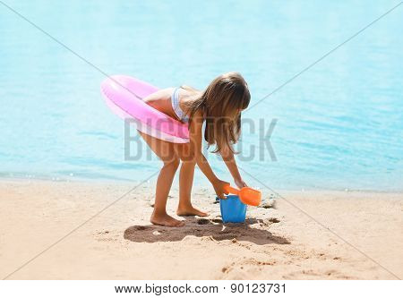 Child With Inflatable Rubber Circle Having Fun On The Beach Near Sea