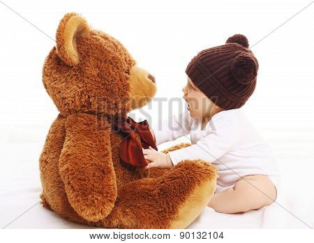 Baby In Knitted Brown Hat Playing With Big Teddy Bear