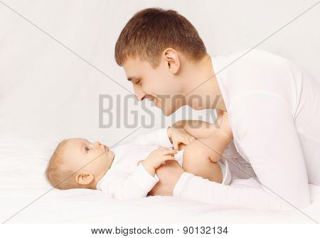 Happy Father Playing With Baby At Home Lying On The Bed Together