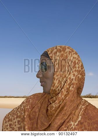 African woman wearing a leopard print headscarf and sunglasses