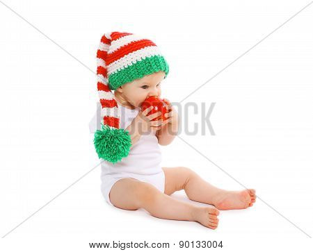 Christmas And Childhood Concept - Baby In Bright Knitted Elf Hat Eating Red Apple