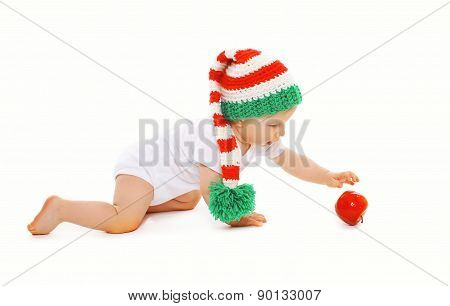 Christmas And Childhood Concept - Baby In Bright Knitted Elf Hat With Red Apple
