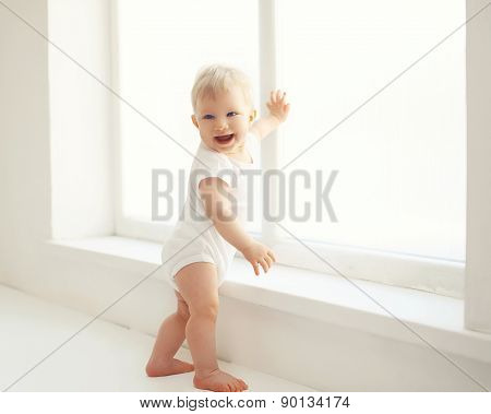 Smiling Baby Standing In White Room At Home Near Window