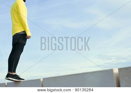 Sportsman in yellow wind breaker taking break with crossed hands standing on sky background.