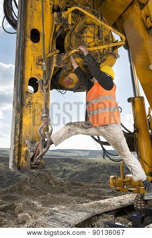 Construction worker climbing on drilling pile foundation