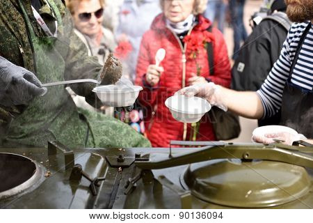 ST. PETERSBURG, RUSSIA - MAY 7, 2015: People at the field kitchen during the parade of steam locomotives. The event dedicated to the WWII Victory Day