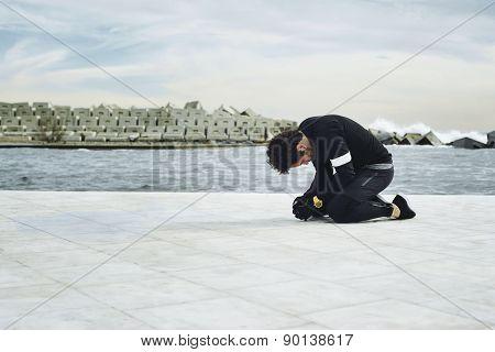 Man runner taking a break during training outdoors in seaside landscape