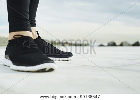 Running shoes. Runner legs and running shoe closeup of man jogging outdoors on road.