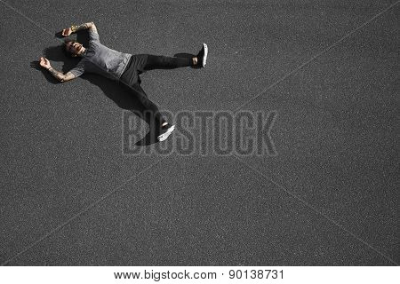 Sport Fitness Man Relaxing After Training. Young Male Athlete Resting Lying In Asphalt